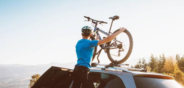 Hombre ciclista de montaña tomar de su bicicleta desde el techo del coche - foto de stock