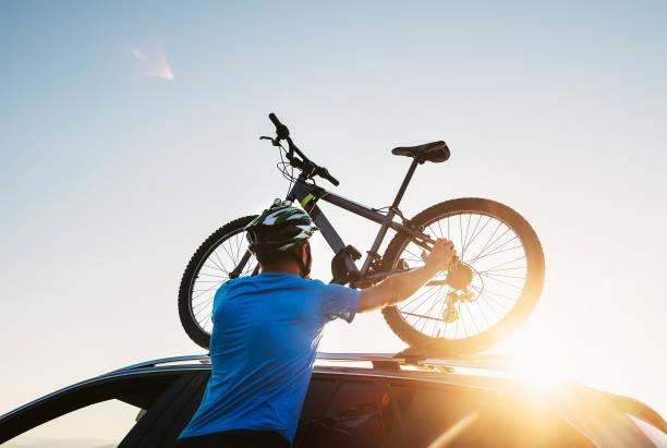 mountain biker mann nimmt von seinem fahrrad aus dem autodach - fahrradträger stock-fotos und bilder