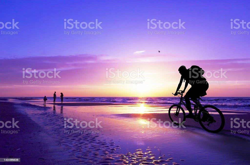 Mountainbiker auf den Strand und Sonnenuntergang. – Foto
