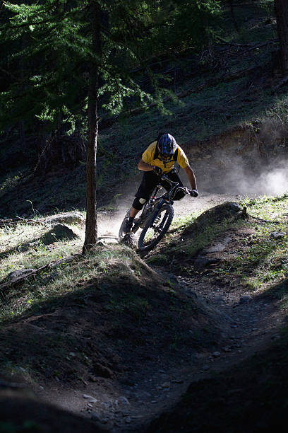 Mountain biker on dirt path  mountain biking stock pictures, royalty-free photos & images