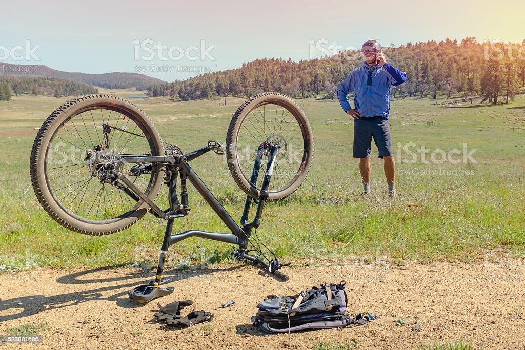 Mountainbiker auf seinem Telefon mit einer Reifenpanne Lizenzfreies stock-foto