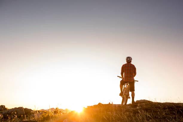 motociclista da montanha no topo da montanha. - escapismo - fotografias e filmes do acervo