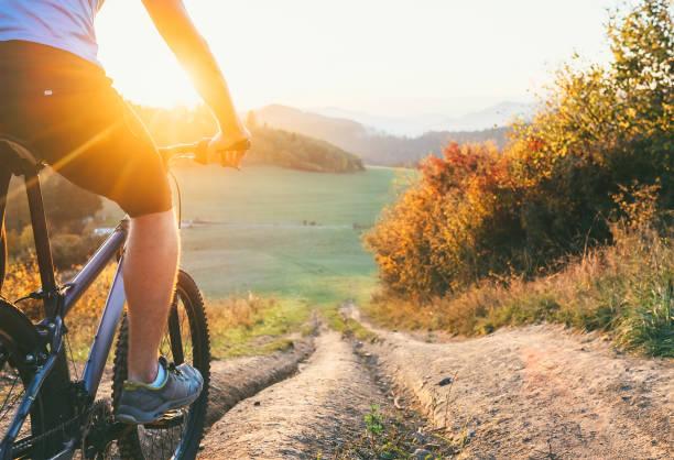 mountainbiker fahren sie vom hügel. aktive und sportliche freizeit-konzept - cyclocross stock-fotos und bilder