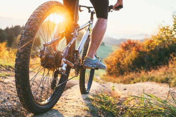 mountainbiker fahren sie vom hügel. schließen sie herauf rad bild. aktive und sportliche freizeit-konzept - cyclocross stock-fotos und bilder