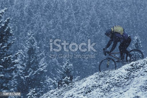 istock Mountain biker rides down snowy hill 1081517458