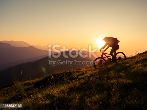Mountain biker riding downhill in mountain at sunset, living adventure.