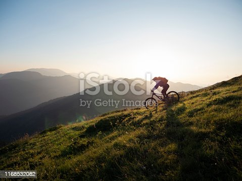 Male mountain biker riding downhill, enjoying on ride and living adventure in the mountain.