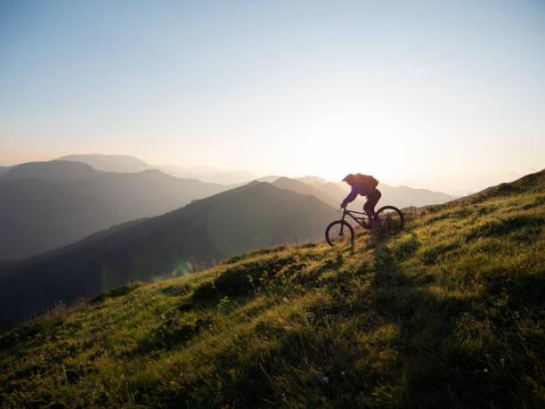 Mountain biker riding downhill Male mountain biker riding downhill, enjoying on ride and living adventure in the mountain. mountain biking stock pictures, royalty-free photos & images