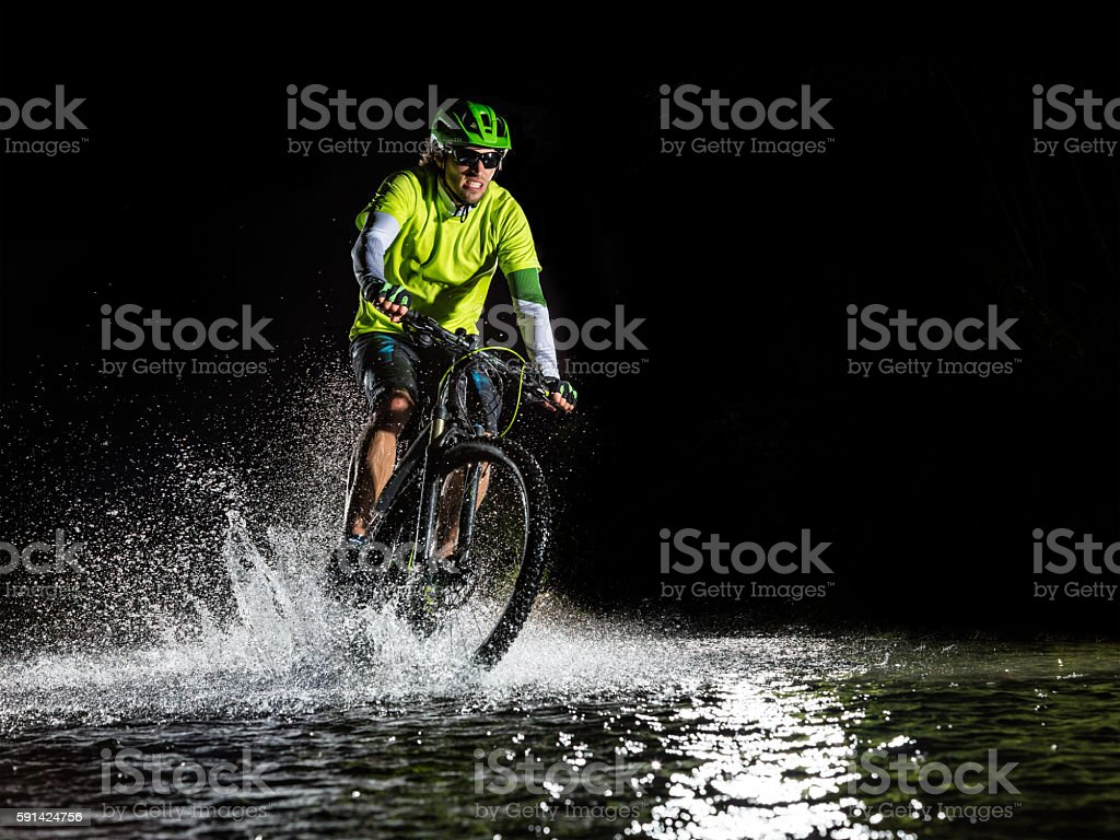 Mountain biker riding in forest stream - Photo