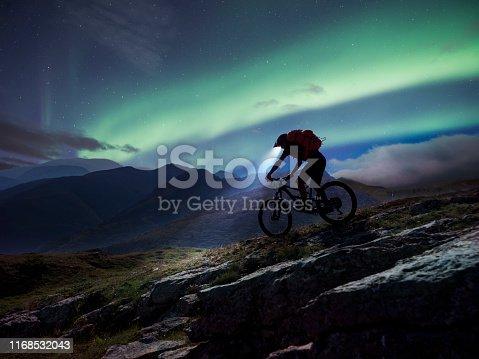 Downhill biker in action riding in the mountain under Aurora Polaris outdoor.