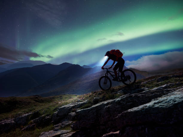 Mountain biker riding in mountain under aurora Polaris.