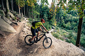 Cycling in autumn inspirational mountains landscape. Mountain biker riding on bike on forest dirt trail. Man cycling MTB on enduro track. Sport fitness motivation and inspiration.