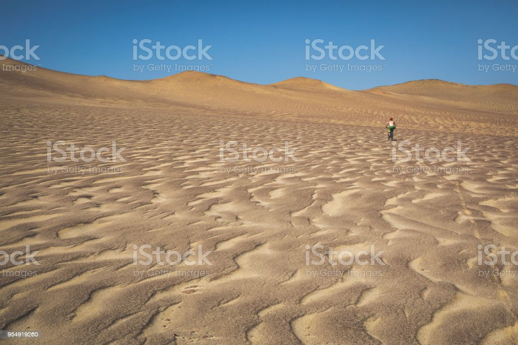 Mountain biker riding through desert in Paracas, Peru. stock photo