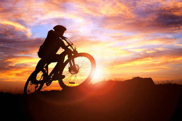 Mountain biker silhouette in action against the sunset concept for sport and exercise Mountain biker silhouette against the sunset concept for achievement, conquering adversity and  exercising mountain biking stock pictures, royalty-free photos & images