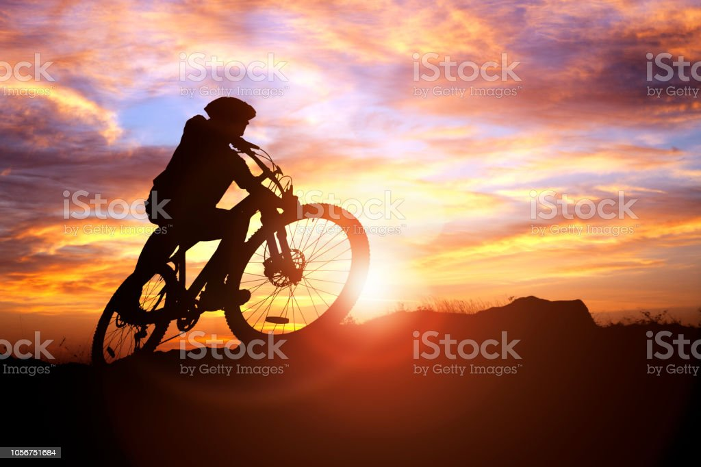 Mountain biker silhouette in action against the sunset concept for sport and exercise stock photo