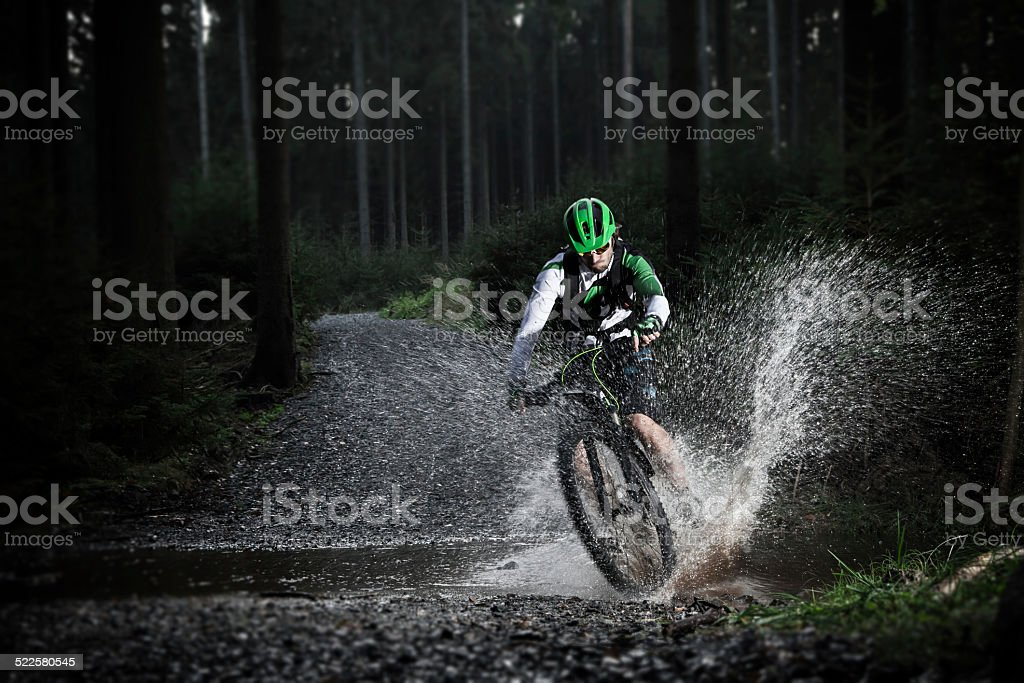 Mountain biker speeding through forest stream. stock photo