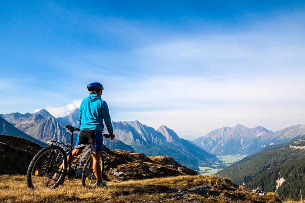 Mountain biker stopped on rocky hillside Mountain biking - woman on bike, Dolomites, Italy mountain biking stock pictures, royalty-free photos & images