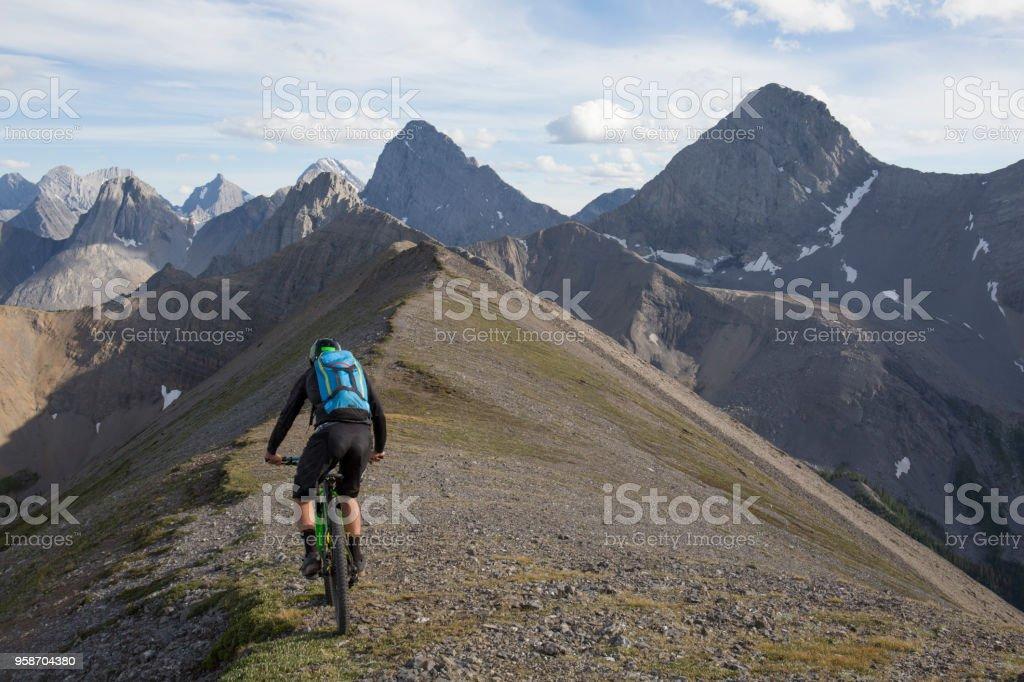 Mountain biker traverses high mountain ridge crest stock photo
