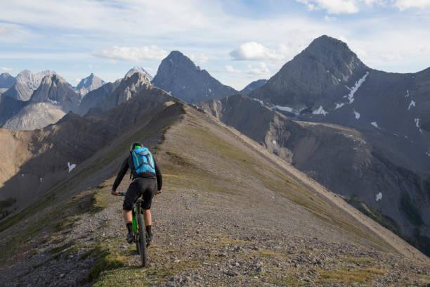 Mountain biker traverses high mountain ridge crest Kananaskis Country, Alberta kananaskis country stock pictures, royalty-free photos & images