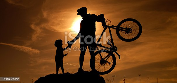 istock Mountain biker with a little son 923633922
