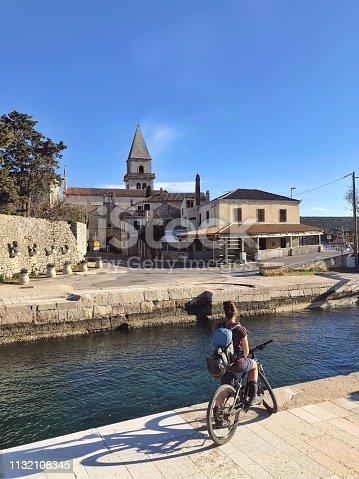 Mountain biker woman enjoying the view of a beautiful town Osor Lošinj island Croatia