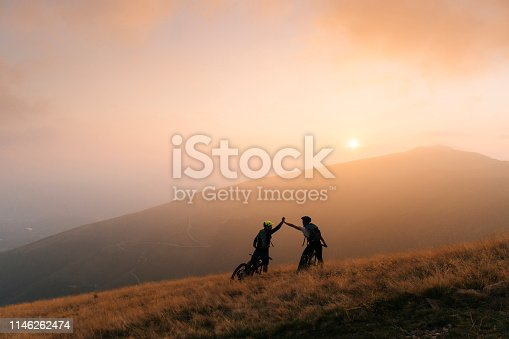 istock Mountain bikers give high-five at sunset 1146262474