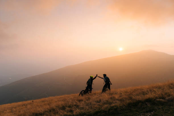 Mountain bikers give high-five at sunset Hazy valley behind central europe stock pictures, royalty-free photos & images