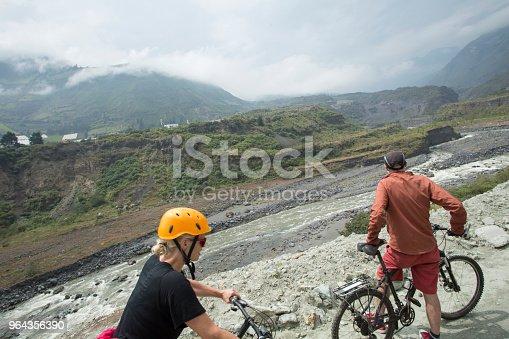 969439086 istock photo Mountain bikers pause on river bank near Banos 964356390