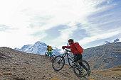 istock Mountain bikers push their bikes up an alpine slope below the Matterhorn mountain 1159059625
