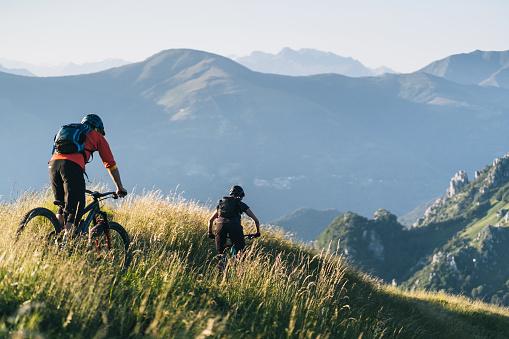 Mountain bikers ride down grassy mountain ridge