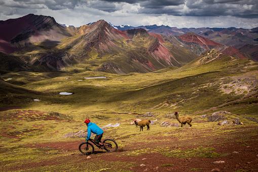 Mountain biker riding through Peruvian Andes.  Ausangate bike packing trip, Peru.