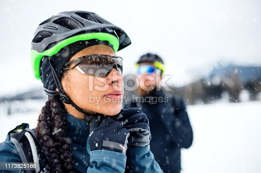 Two mountain bikers standing outdoors in winter, putting on helmet.