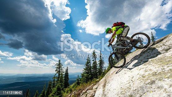 Downhill mountain biking on sunny day at ski resort.