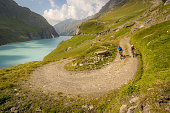 Two mountain bikers, a man and a lady riding their mountain bikes on a trail beside a lake in the Valais region of Switzerland.