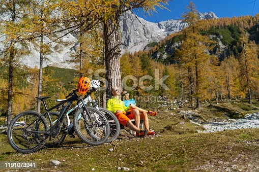 happy sporty mature adult couple with electric mountainbikes sitting together on bench in alpine mountain landscape with some larch trees on sunny autumn day enjoying short rest in sunshine