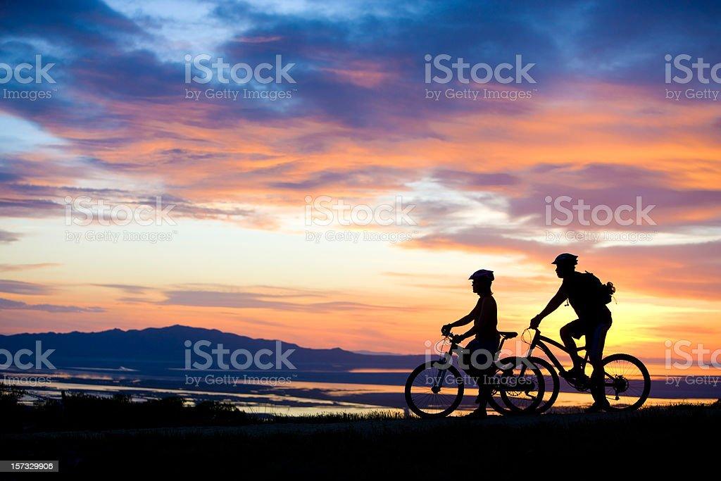 Mountain Biking Couple Enjoying Sunset View Mountain Biking Couple Enjoying Sunset View 30-39 Years Stock Photo