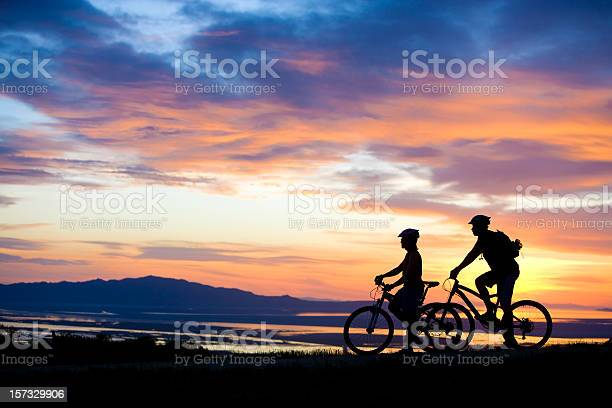 Mountain Biking Couple Enjoying Sunset View Stock Photo - Download Image Now