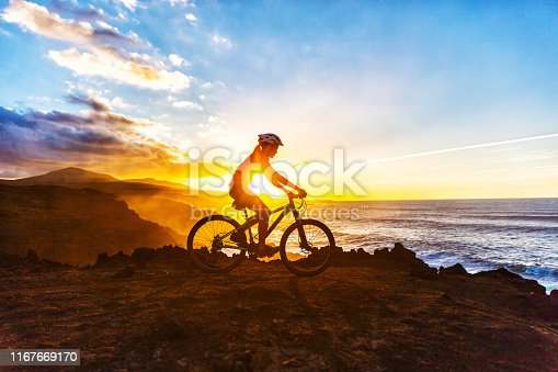 Mountain biking MTB cyclist woman cycling on bike trail on coast at sunset. Person on bike by sea in sportswear with bicycle enjoying healthy active lifestyle in beautiful nature.