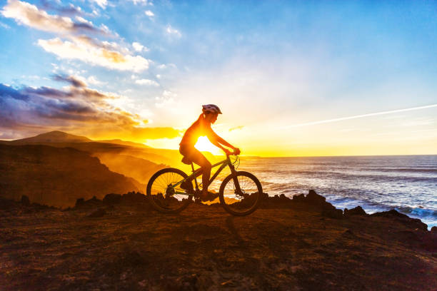 Mountain Biking Cyclist Woman Bike Trail Cycling Mountain biking MTB cyclist woman cycling on bike trail on coast at sunset. Person on bike by sea in sportswear with bicycle enjoying healthy active lifestyle in beautiful nature. mountain biking stock pictures, royalty-free photos & images