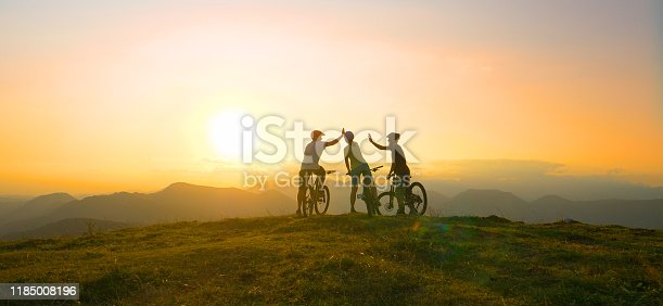 SUN FLARE: Mountain biking friends high five after reaching the scenic summit at breathtaking golden sunrise. Cross country cyclists celebrate a successful mountain biking adventure on a sunny evening