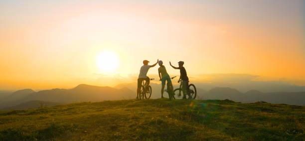sun flare: mountainbike-freunde hoch fünf nach erreichen des gipfels bei sonnenaufgang - radfahren stock-fotos und bilder