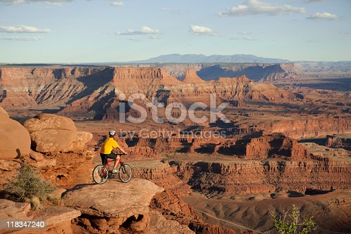 Man sitting on bicycle looking at magnificent view in Canyonlands National Park, Moab, Utah.