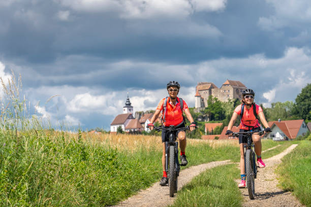 Mountain biking in Franconia, Bavaria 06-29-2020, Hiltpoltstein, Franconia, Bavaria, Germany - Franconia with its many medieval castles, like here Hiltpolstein is good place for leisure activities like mountain biking and hiking ebike for elder stock pictures, royalty-free photos & images