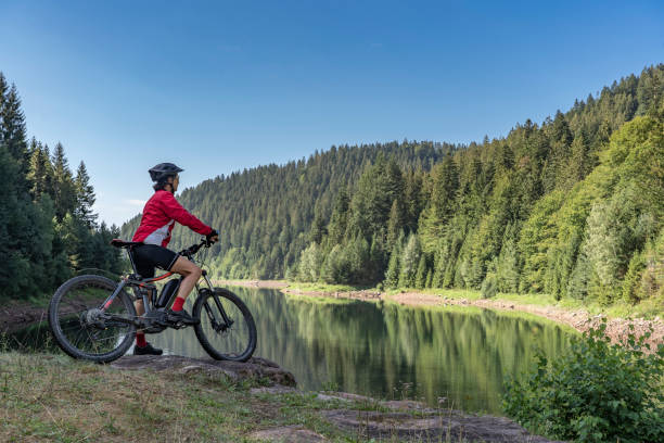 mountain biking in the black forest nice and ever young senior woman with her electric mountain bike at the Kinzig drinking Water reservoir in the northern Black Forest, Baden-Wuerttemberg, Germany mountain biking stock pictures, royalty-free photos & images