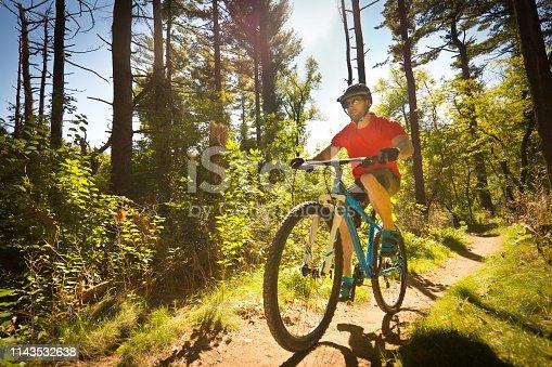 A Caucasian young man mountain biker biking along a wooded mountain trail. Photographed in Minneapolis Minnesota USA in horizontal format.