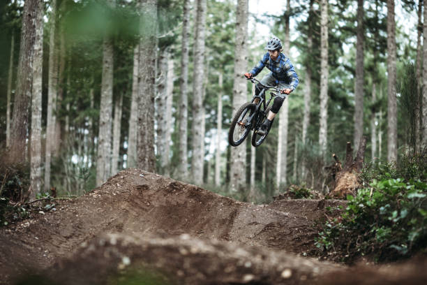 Mountain Biking Man Gets Big Air off Jump An adult man races down a forest trail, flying through the air from a dirt jump on his mountain bike.  Fun and healthy lifestyle image of recreational outdoor activity. mountain biking stock pictures, royalty-free photos & images
