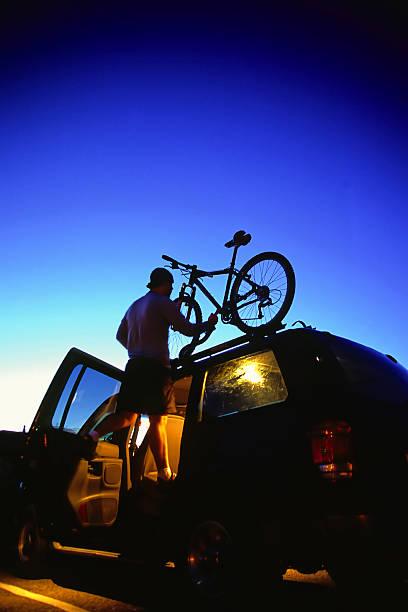 mountainbiken mann beladen fahrrad auf suv twilight himmel - fahrradhalter stock-fotos und bilder