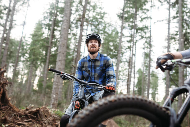 Mountain Biking Man Takes Break on Trail An adult man takes a break from a forest trail ride on his mountain bike, talking with a friend.  Fun and healthy lifestyle image of recreational outdoor activity. mountain biking stock pictures, royalty-free photos & images