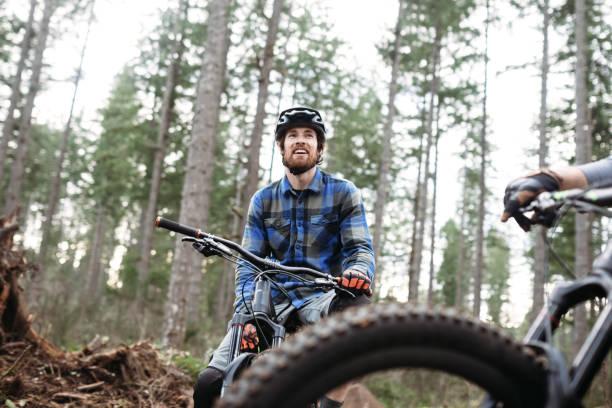 mountain biking man takes break on trail - mountain bike stock pictures, royalty-free photos & images