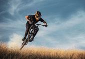 Skilled mountain biker jumping.